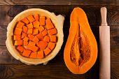 foto of pumpkin pie  - Raw pumpkin pie on the brown wooden background  - JPG