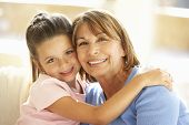stock photo of granddaughter  - Hispanic Grandmother And Granddaughter Relaxing At Home - JPG