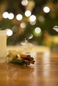 image of bundle  - Bundle of cinnamon wrapped in ribbon on a wooden table with a candle - JPG