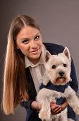 image of westie  - Girl and West Highland Terrier wearing similar blue jackets studio shot grey background - JPG