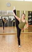 picture of do splits  - Young slim woman doing standing split in fitness class - JPG