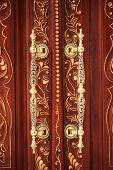 picture of wooden door  - Golden vintage door handles on a wooden door with a carved pattern - JPG