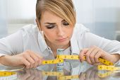 pic of measuring height  - Portrait Of Businesswoman Holding Measuring Tape Around Dollar Banknote - JPG