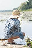 picture of rod  - Sitting on wooden bridge shoeless young fisherman with fishing rod - JPG