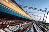 image of passenger train  - High speed passenger train on tracks with motion blur effect at sunset - JPG