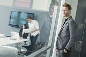 pic of ginger man  - Young man standing by the glass door in the office - JPG