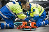 stock photo of paramedic  - Paramedics preparing a stretcher for a wounded car accident victim - JPG