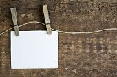 pic of clotheslines  - white paper sign hanging on clothesline with clothespins on rustic wooden background - JPG