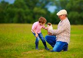foto of grandpa  - grandpa presenting little puppy to grandson playing with dog - JPG