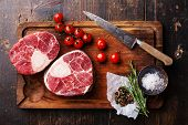 picture of cut  - Raw fresh cross cut veal shank and seasonings for making Osso Buco on wooden cutting board - JPG