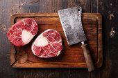 stock photo of veal  - Raw fresh cross cut veal shank for making Osso Buco and meat cleaver on wooden cutting board - JPG