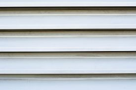 foto of louvers  - Close up of outdoor white louver vents on a seafood restaurant door circulating fishy aromas out of the restaurant - JPG