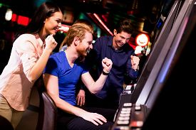 picture of gambler  - Young people at slot machine in the casino - JPG