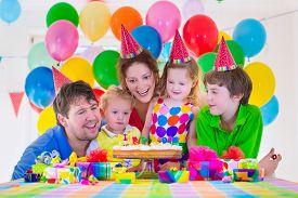 stock photo of celebrate  - Happy family celebrating kids birthday - JPG