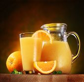 Still life: oranges, glass of juice and jug full of juice on a wooden table.