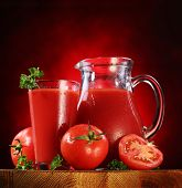 Still life: tomatoes, jug and glass full of fresh tomatoes juice on wooden table.
