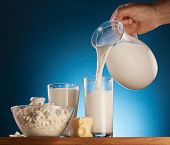Man hand pouring milk from jar into the glass. Isolated on a  blue.