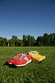 Red And Yellow Running Shoes On A Sports Field