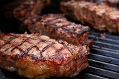 pic of barbecue grill  - Thick juicy steaks on a barbecue grill.