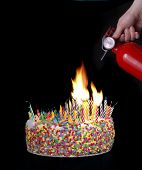 foto of birthday-cake  - a hand holding a fire extinguisher above a cake with candles creating a fire - JPG