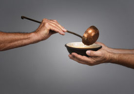 stock photo of stewardship  - man holding a bowl in both hands receiving a serving of soup from another man holding a soup ladle - JPG