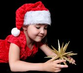 Adorable Girl In Christmas Outfit Playing With Golden Star Ornament