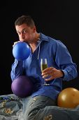 stock photo of bachelor party  - A man at a party blowing up balloons - JPG