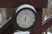 Round Circular Outdoor Thermometer Covered With Snow Shows Low Temperatures Near Zero. Low Temperatu poster
