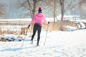 Woman doing cross country skiing as winter sport in snow landscape  poster