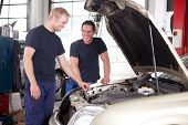 stock photo of people work  - Two mechanics looking at and working on a car in a repair shop - JPG