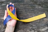 World Down Syndrome Day With Blue Yellow Awareness Ribbon Bow Color On Helping Hand For Raising Supp poster