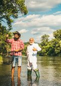 Brown Trout Fish. Angler. Fly Fisherman Using Fly Fishing Rod In Beautiful River. Family And Generat poster