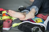 Bare Feet In A Pile Of Shoes. Childrens Foot On The Background Of Sneakers. Foot And Shoes poster