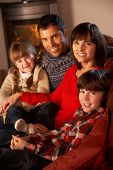 Portrait Of Family Relaxing On Sofa By Cosy Log Fire