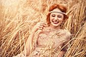 Romantic young woman with beautiful red hair lies on a wheat field and laughs. Beauty, fashion. Mode poster
