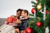 Romantic multiethnic couple exchanging gifts near decorated christmas tree. Smiling man in sweater g poster