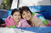 Grandmother and granddaughter laying in tent smiling