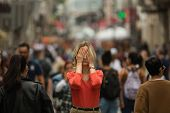 Sad depressed woman covers his eyes with his hands surrounded by people walking in crowded street. P poster