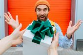 Wow. Unexpected News And A Bright Emotion, Beard Hipster Man Gets Gift Box On Red Background Learned poster