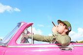 Cuba concept. Vintage car with cigar smoking man with Fidel Castro patrol cap. Funny image cuban conceptual image.