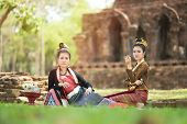Young Asian Women In Traditional Dress Sit On Green Grass With Pillow Hand Hold Tobacco Leaf  Cigare poster