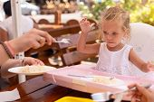 Cute Little Caucasian Girl Eating Spaghetti At Table Sitting In Child Seat Outdoor Restaurant. Healt poster
