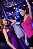 stock photo of night-club  - Young woman having fun and dancing at night club disco - JPG