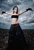 Informal Fashion: The Beautiful Slender Young Gothic Girl Dressed In Black Leather Skirt And Gloves. poster