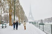 Scenic View To The Eiffel Tower On A Day With Heavy Snow. People Walking With Umbrellas On A Snowy D poster