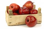 Fresh and delicious red Ambrosia apples in a wooden crate  on a white background