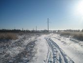 Winter Road In A Clean Flat Field On A Clear Frosty Day. The Sky Is Clear, Blue And Transparent, Wit poster