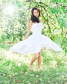Beautiful young woman dancing in the morning bright summer orchard