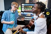 Young singer or musician of African ethnicity playing the guitar and singing while his colleague rec poster