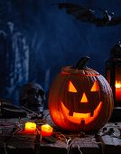 Jack-o-lantern With Burning Candles And Lantern On A Rustic Wooden Surface And Spooky Background poster